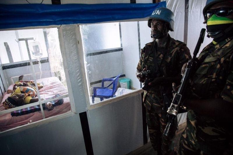 ENSZ-békefenntartók vigyázzák egy ebolafertőzött gyógyulását. A védelemre extrém mértékben szükség van a kontinensen. Forrás: MSF Analysis